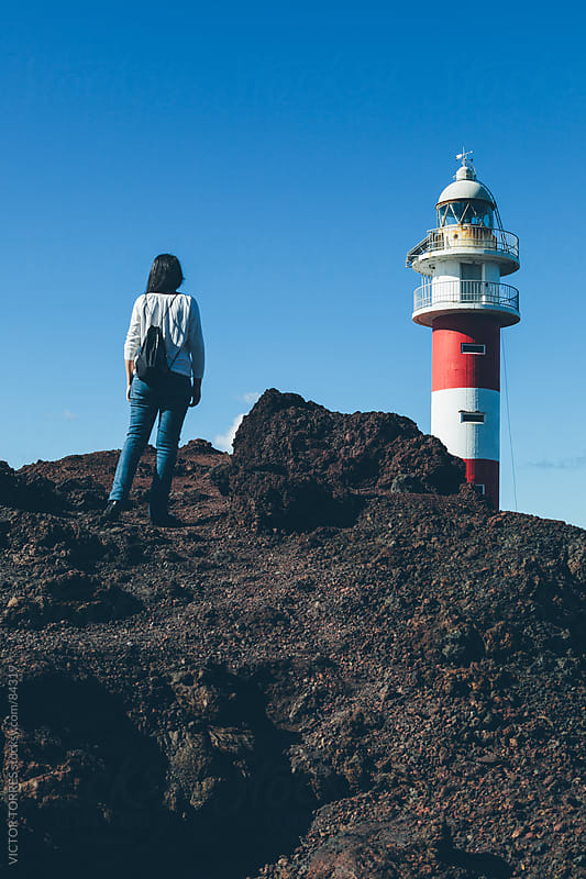 Woman Besides a Lighthouse by VICTOR TORRES for Stocksy United