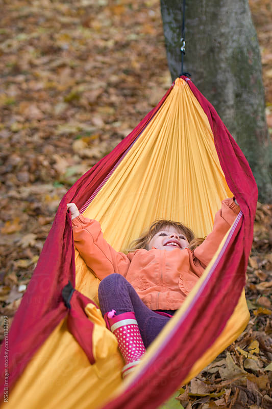 Little girl swinging in a hammock in the park by RG&B Images for Stocksy United