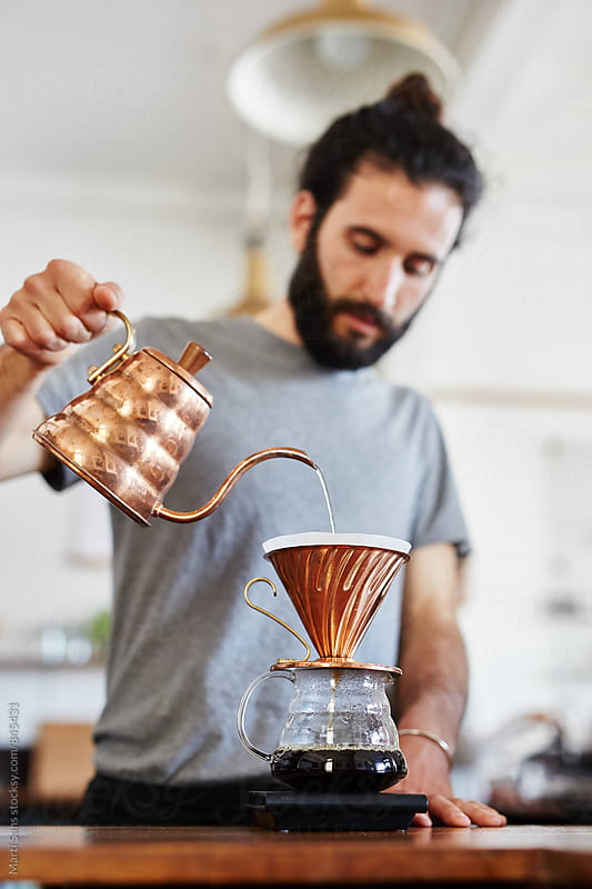 Barista pouring hot water through chemex by Martí Sans for Stocksy United