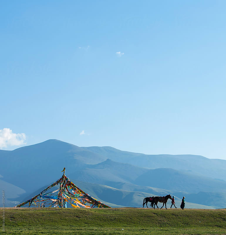 two Tibetan people walking with their horse on the plateau  with streamer flying by Bo Bo for Stocksy United