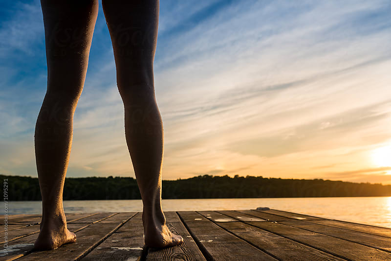 Woman About To Jump Into Warm Summer Cottage Lake At Sunset from Dock by JP Danko for Stocksy United