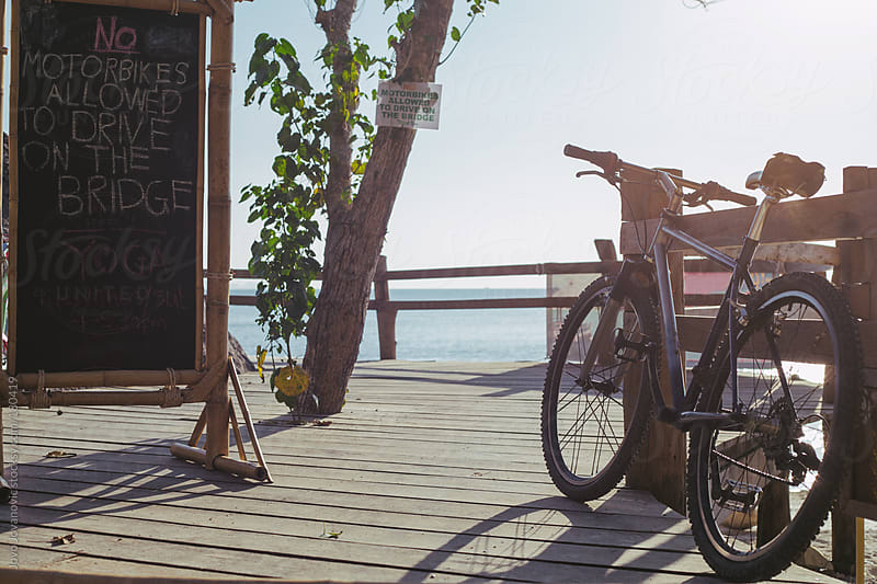 Parked bicycle on a wooden pier by Jovo Jovanovic for Stocksy United
