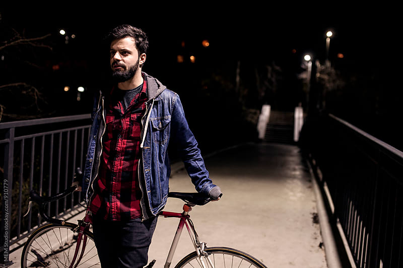 Portrait of a young male cyclist by night by MEM Studio for Stocksy United