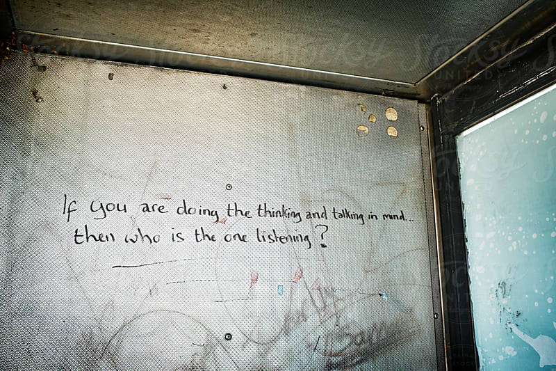 Graffiti inside a public payphone by James Ross for Stocksy United