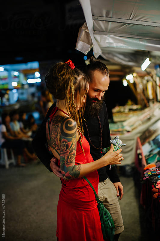Couple Buying Souvenirs at the Night Market by Mosuno for Stocksy United