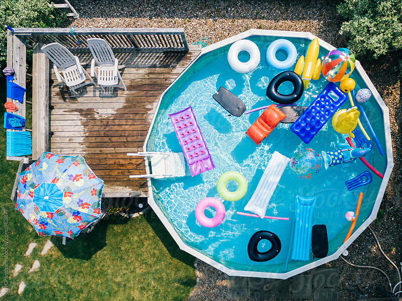 Overhead drone image of an above ground pool filled with pool floats by Jen Grantham for Stocksy United