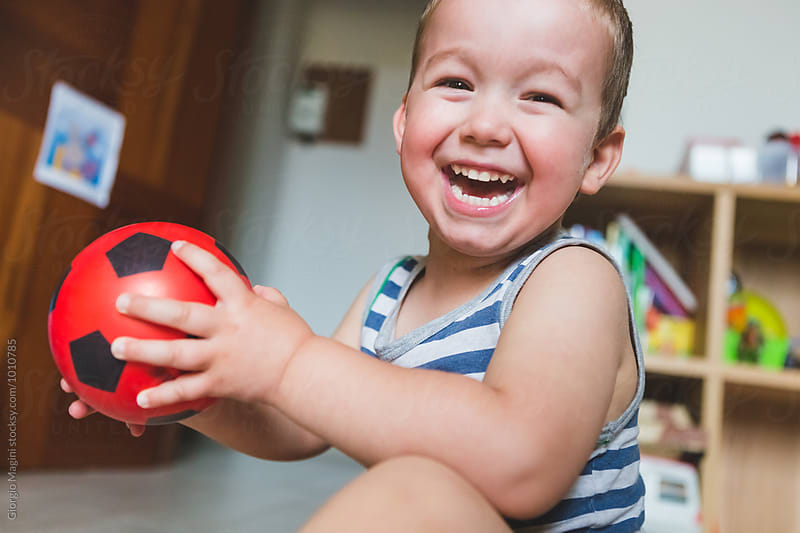 Happy Toddler at Home Playing with a Small Red Ball by Giorgio Magini for Stocksy United