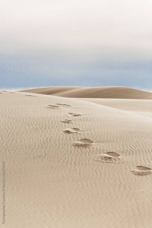 Foot steps in sand dunes by Photographer Christian B for Stocksy United