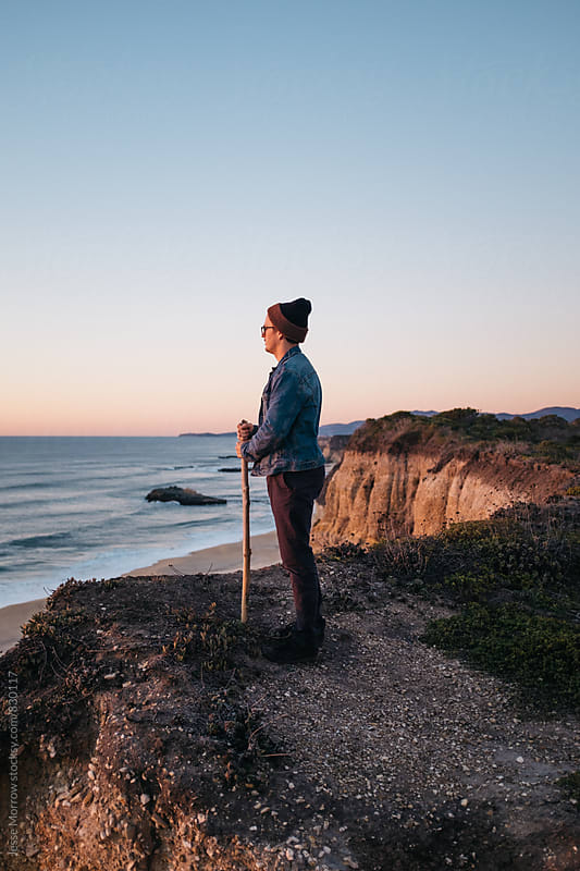 young man looking out at ocean waves at coastal viewpoint by Jesse Morrow for Stocksy United