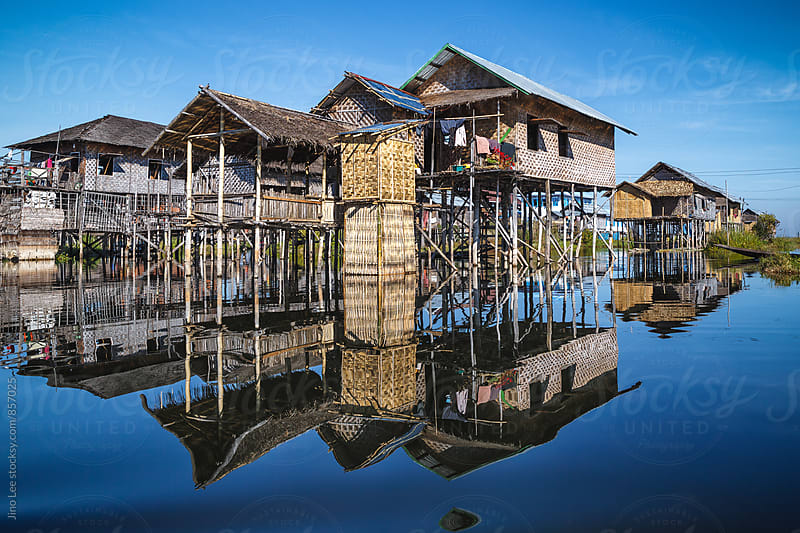 Reflections of local Inle Lake houses by Jino Lee for Stocksy United