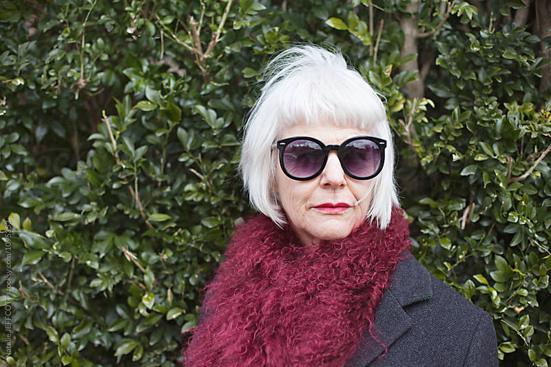 stylish and attractive older woman outdoors wearing a scarf and sunglasses by Natalie JEFFCOTT for Stocksy United