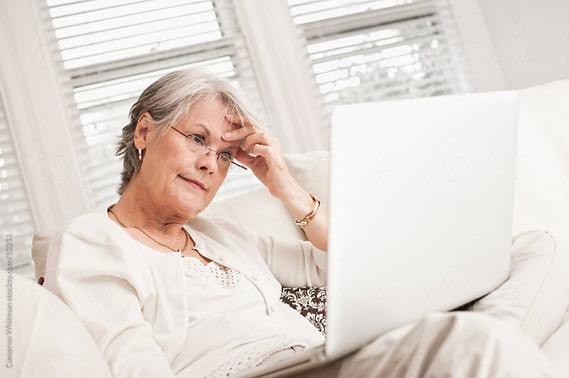 Mature Woman Reading Bad News On Laptop by Cameron Whitman for Stocksy United