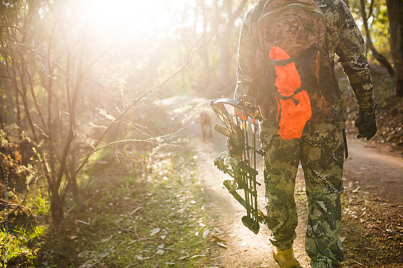 Hunter walking through bush with bow by Reece McMillan for Stocksy United