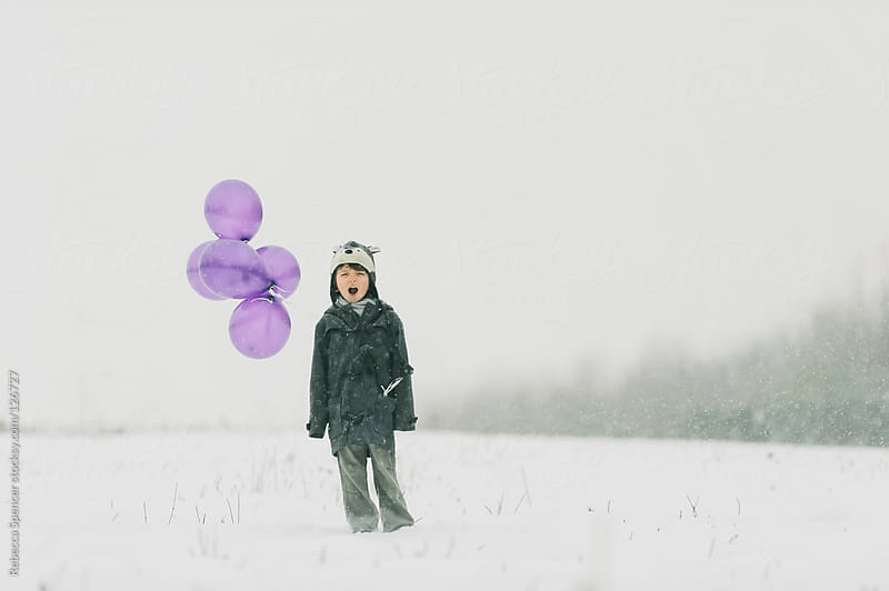 Child in snow with purple balloons by Rebecca Spencer for Stocksy United