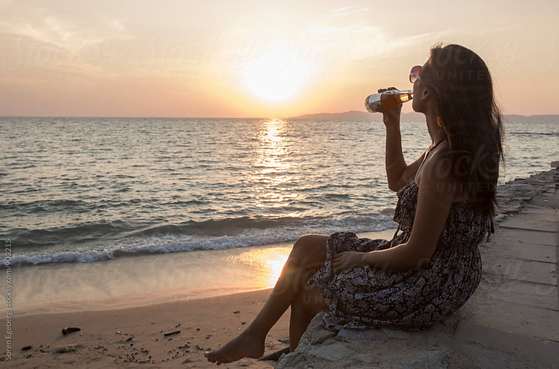 Woman drinking a beer on beach at sunset  by Soren Egeberg for Stocksy United
