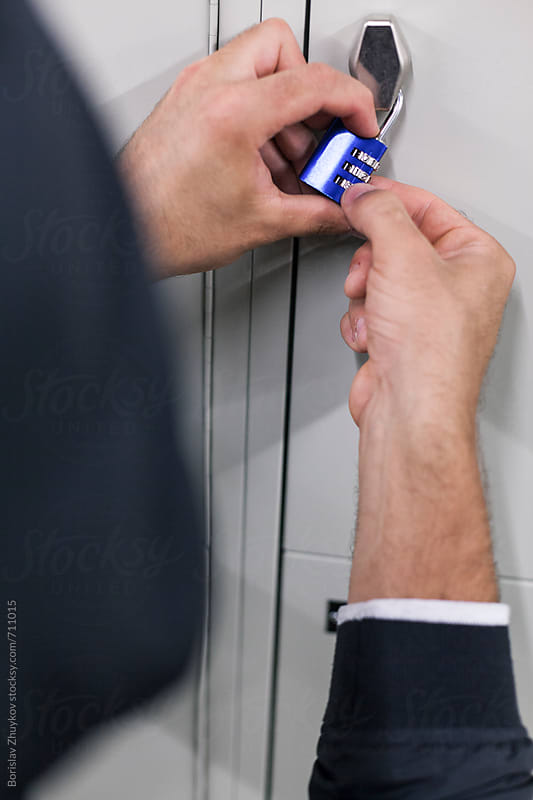Man With Hood Trying To Open Locker Padlock by Borislav Zhuykov for Stocksy United