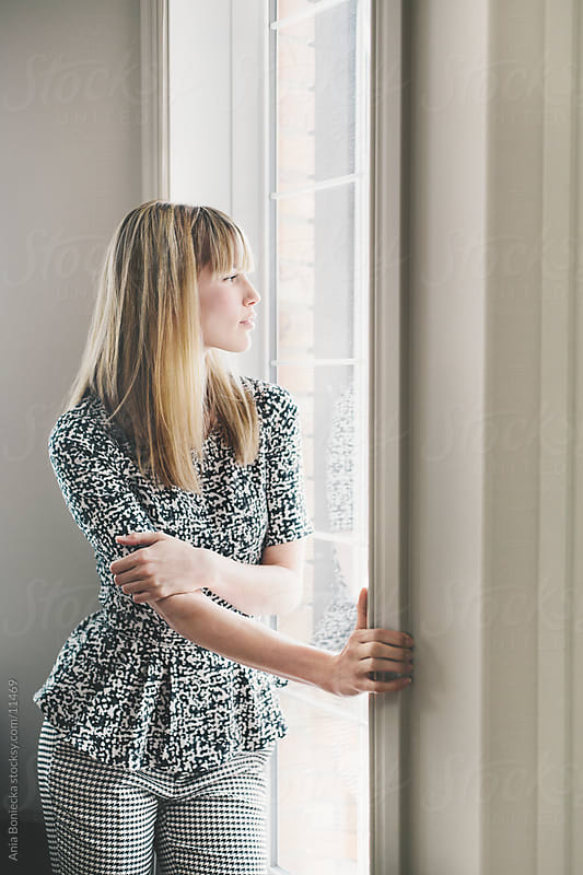 A beautiful woman looking out the window by Ania Boniecka for Stocksy United
