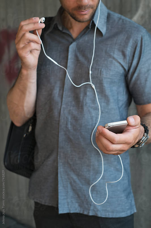 Man is changing music on his phone by Jelena Jojic Tomic for Stocksy United