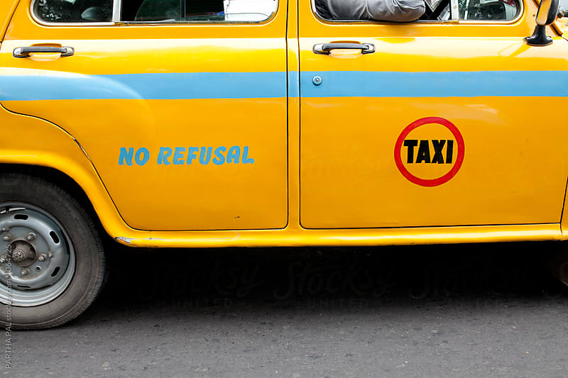 A yellow colored taxi with No Refusal wrieen in body by PARTHA PAL for Stocksy United