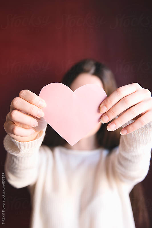 Close-up of woman holding pink paper heart by T-REX & Flower for Stocksy United