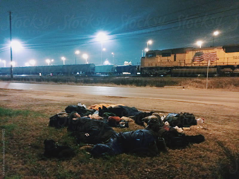 People Sleeping by Train Yard by Kevin Russ for Stocksy United