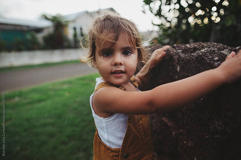 Cute young toddler girl standing near rock wall by Rob and Julia Campbell for Stocksy United