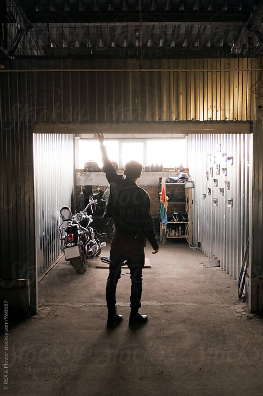 Back view of young rocker closing garage by Danil Nevsky for Stocksy United