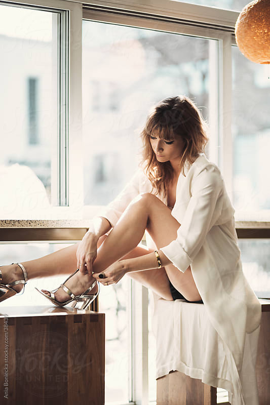 A young woman doing up her sandals by a counter at a lounge by Ania Boniecka for Stocksy United
