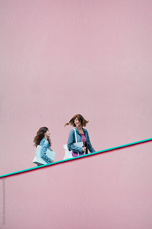 Mother and daughter with shopping bags going up in front of a pink wall  by Beatrix Boros for Stocksy United
