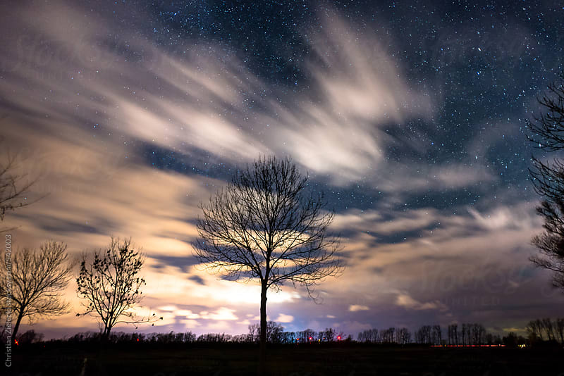 night sky behind moving clouds by Christian Zielecki for Stocksy United