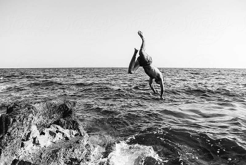 Young man jumping into the sea by Lucas Ottone for Stocksy United