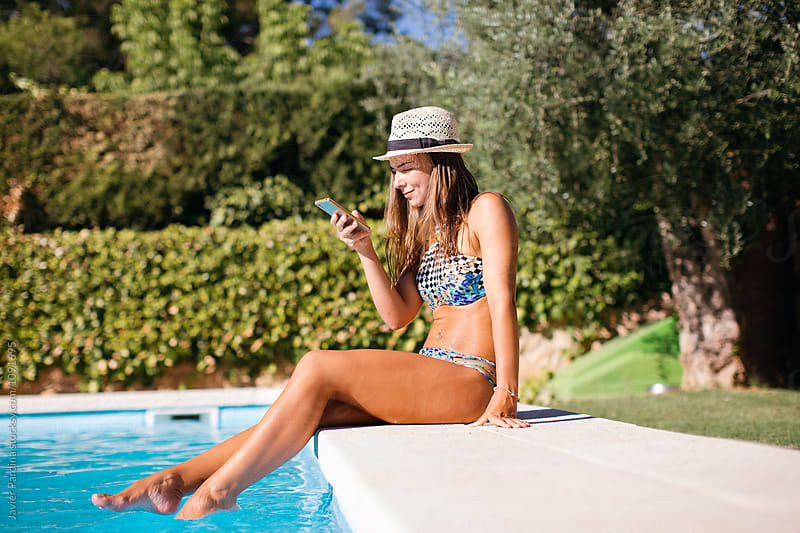 woman enjoying with phone in pool by Javier Pardina for Stocksy United