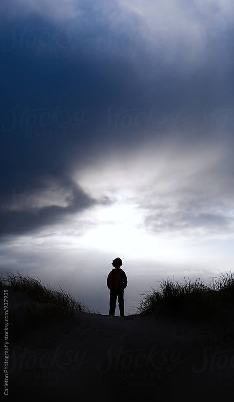 Solitary figure stands atop a sand dune at sunset by Carleton Photography for Stocksy United
